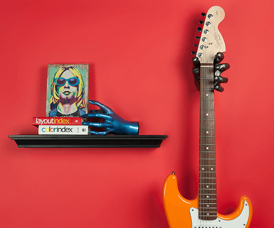 Fender stratocaster hanging from red wall next to shelf and picture of Kurt Cobain
