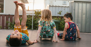 Three young kids wearing colourful organic clothes, sitting together on a trampoline in a late afternoon sunset. They are looking away from the camera. One child is lying on their back with their legs stretched high up to the sky.