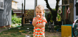 Young child wearing a DUNS of Sweden tomato printed short sleeve top. Child is standing outside in a backyard, looking at the camera, with their arms folded.