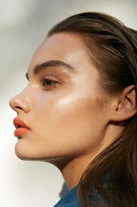 Woman with gold glowing make up.
