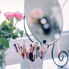 Mirror with makeup brushes and roses