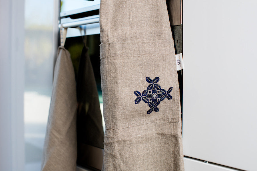 linen apron hand-embroidered in jordan by refugees