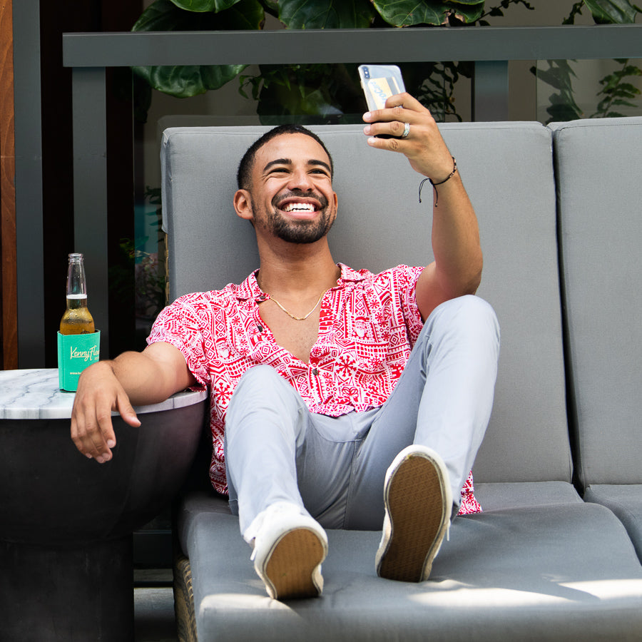 red christmas hawaiian shirt by kenny flowers being worn on a lounge chair and captured in a selfie