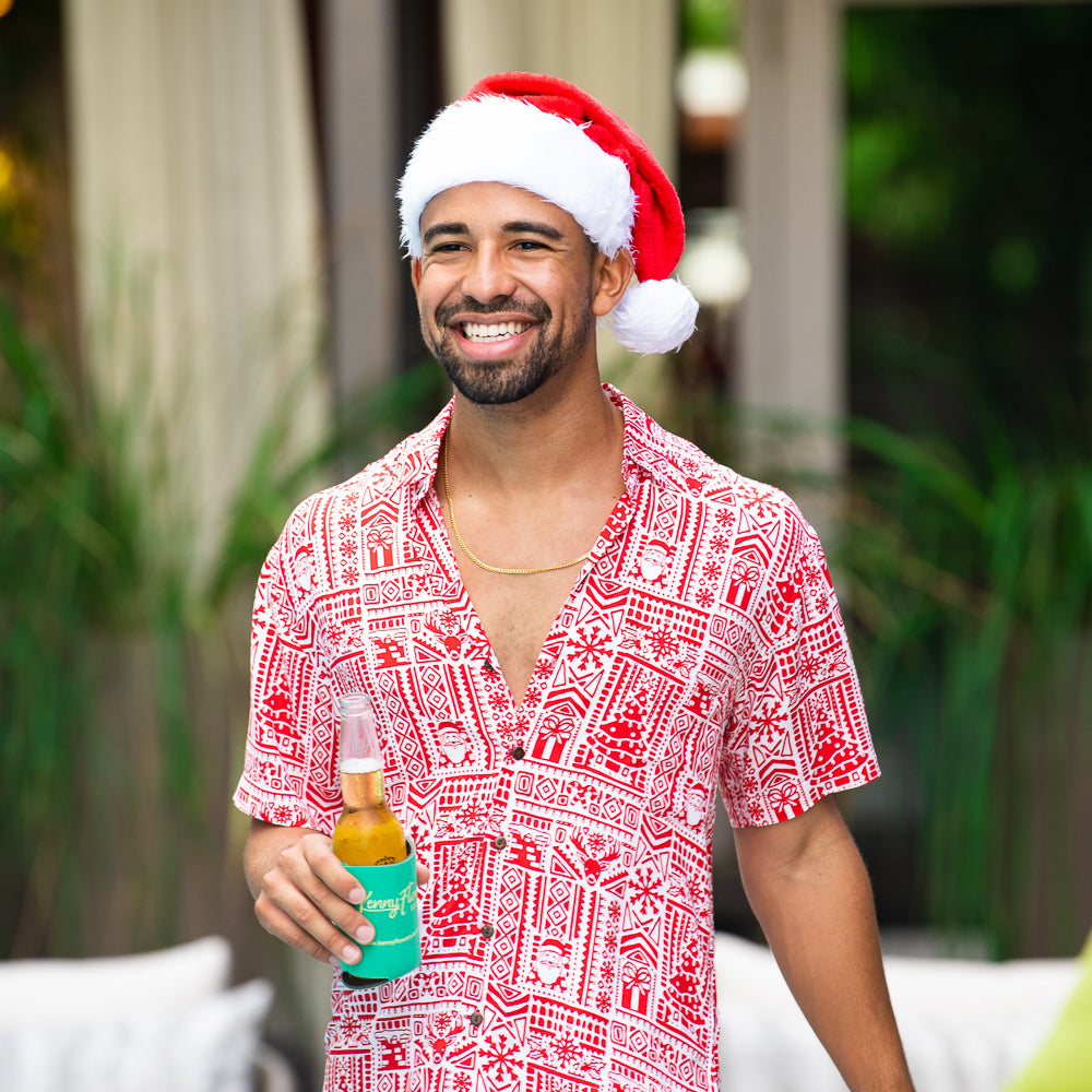 red christmas-themed hawaiian shirt and santa hat being worn in miami brand kenny flowers