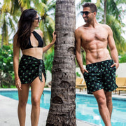 Matching couple with black palm print mens swim trunks and womens sarong
