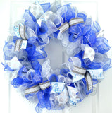 Winter wreath with royal blue, white and silver mesh on a white front door