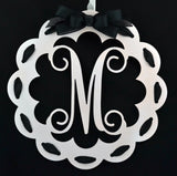 white monogrammed door hanger with black ribbon and bow