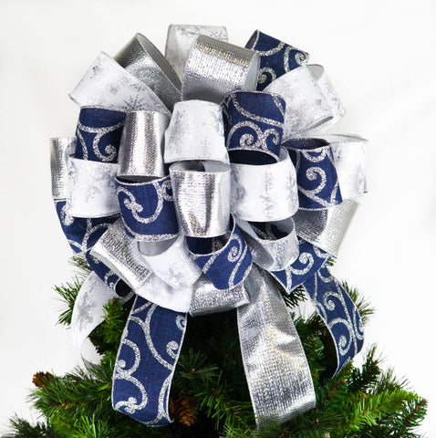 Christmas Tree Bow on top of a tree with navy silver and white ribbons