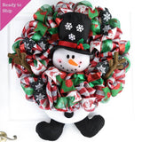 Ready to ship Red and silver winter wreath with snowman head in the middle and legs sticking out of the bottom on a white door