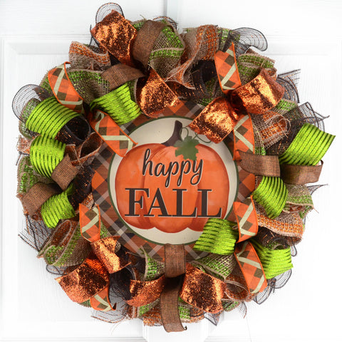 Round brown orange and green mesh wreath with a circle metal sign in the middle with a pumpkin and the words Happy Fall, hanging on a white door