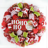 Red White and Lime Green Mesh Wreath with a wooden Ho Ho Ho sign with a Santa Face on the sign, all hanging on a white door