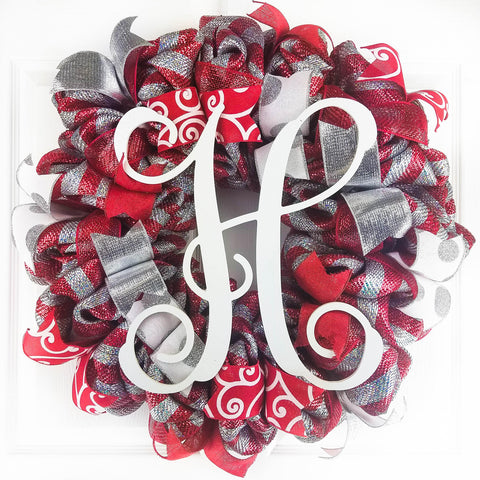Red and silver Christmas mesh wreath with a white Monogram H in the middle, hanging on a white door