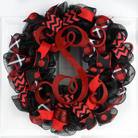 Black mesh wreath with red and white accented ribbons, with a red monogram in the center