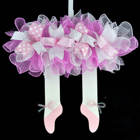 Wooden wreath with skirt at the top made from mesh, with ballerina legs and shoes hanging from the bottom