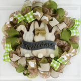 jute wreath with green accents showcasing a wooden Easter Bunny welcome sign in the middle