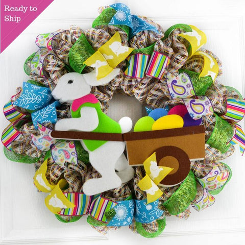 Multi color wreath with a bunny pulling a cart of eggs
