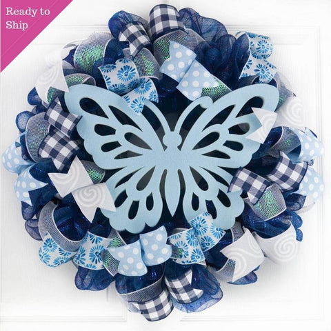 Navy blue wreath with white, light blue and buffalo plaid ribbon with a light blue butterfly in the middle