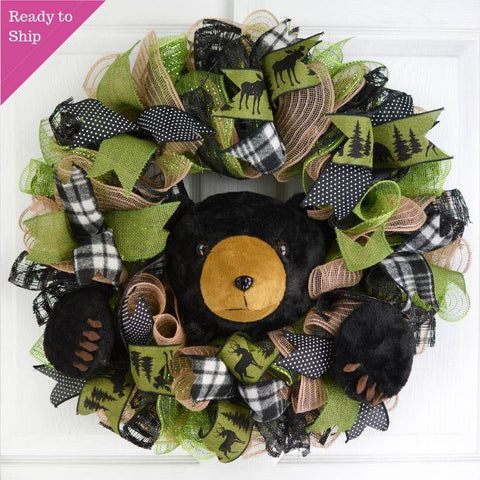 Green and brown woodsy wreath with black bear poking out of middle