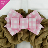 Pink and white buffalo plaid bow on a burlap wreath