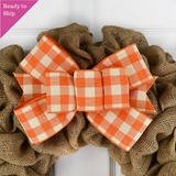 Orange and white buffalo plaid bow on a burlap wreath