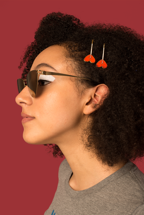 Two red heart bobbi pins modeled in curly hair