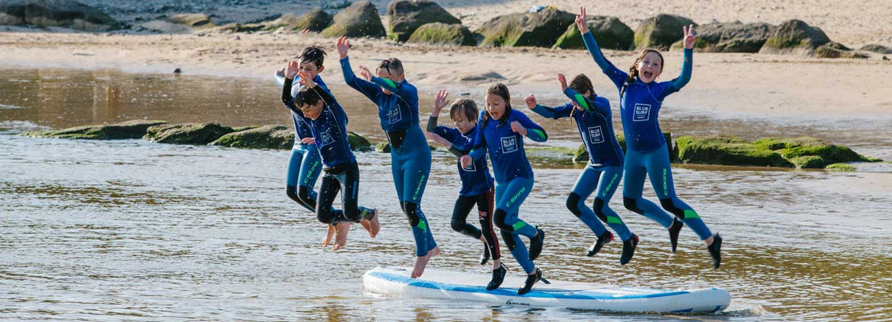 Little girl stoked to stand up on a Blue Surf School Lesson