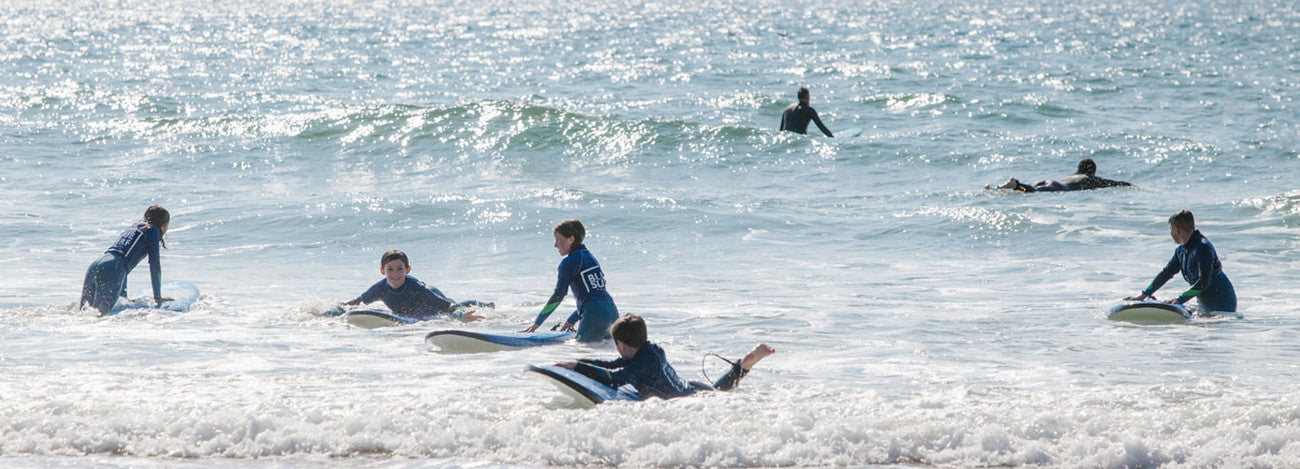 Boy learning to surf with Blue Surf School