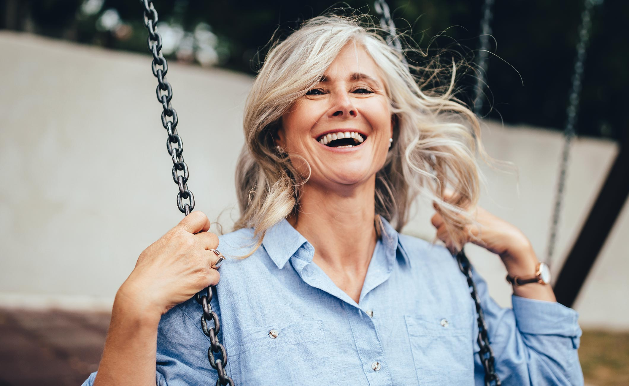 older woman swinging on a swing and smiling
