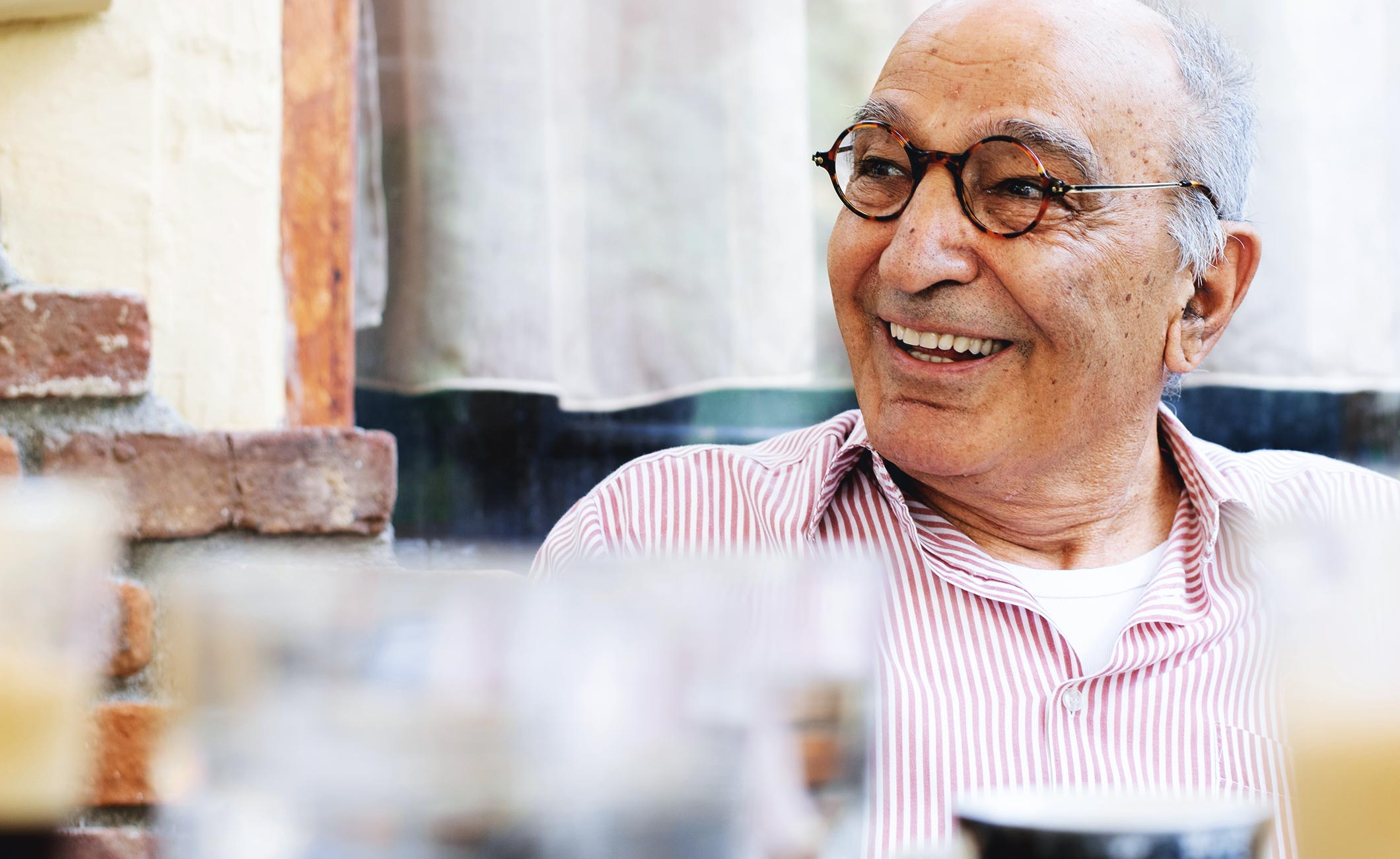 older man with glasses smiling