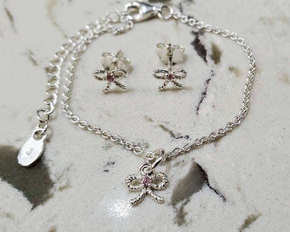 Baby or child's sterling bow bracelet and earrings set with pink CZ stones in the center.  Antiqued finish. Bows are twisted shape. Bracelet finished with lobster clasp and 2 inch extender.