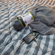 Image of lantern laying on sleeping bag with smart phone plugged in for device charging