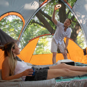 Lifestyle image of 9 person dome tent interior with person laying on air bed and another person hanging tent light on ceiling with rainfly off showing panoramic mesh ceiling with views of trees