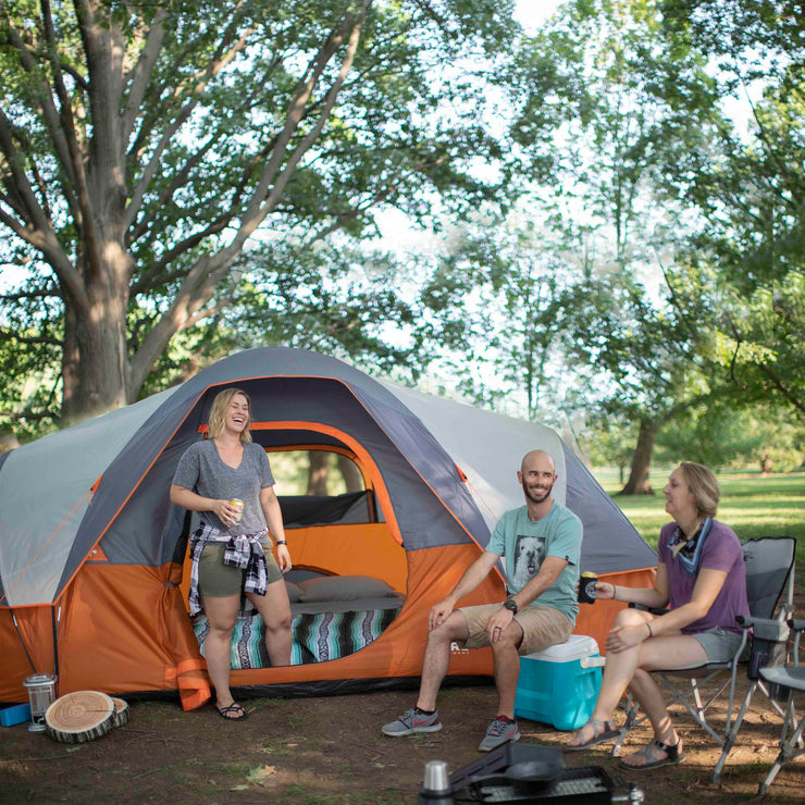 Lifestyle image of friends camping in 9 person extended dome with rainfly on and queen sized air mattress inside