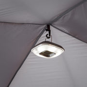 Tent light hanging from lantern hook on interior ceiling of tent