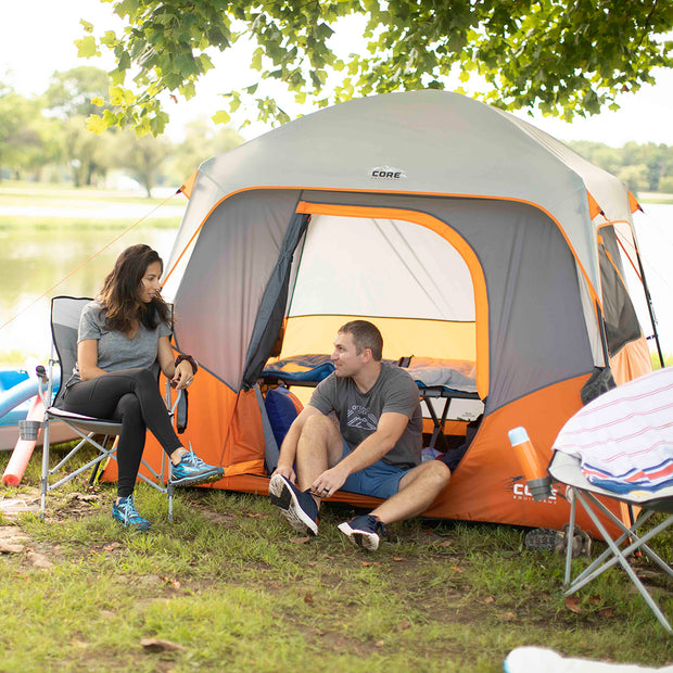 Lifestyle image of couple camping, one sitting in 4 person straight wall tent, one sitting in core camp chair outside of tent