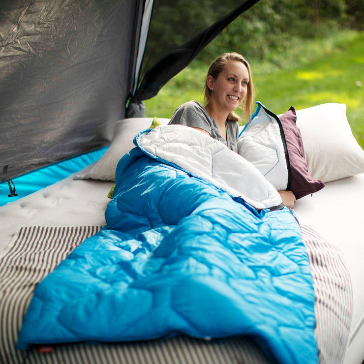 Lifestyle image of woman laying in sleeping bag while camping