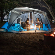 10 Person Lighted Instant Cabin Tent Lifestyle with two friends sitting in chairs in screen room at night