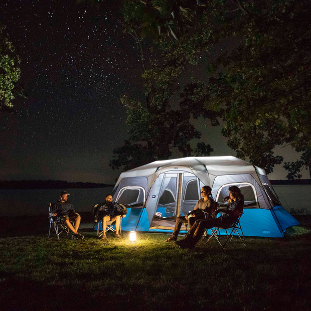 Lifestyle image of 12 person instant cabin tent with cabin light on and friends outside camping