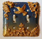 Polymer clay hummingbird, leaves and flowers on a light switch cover.
