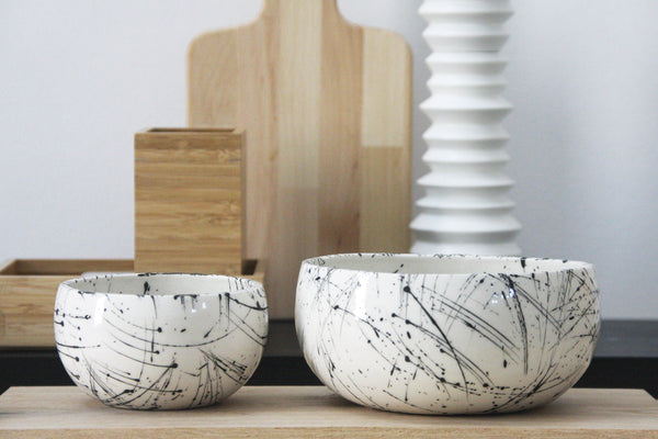 Ceramic set of two different sized bowls in white and black lines pattern.