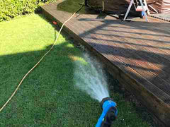 Drenching grass with water prior to softwashing wooden decking with Benz Perma Cleanze