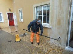 Softwashing wall render to clean algae, mold, fungi, moss and lichen