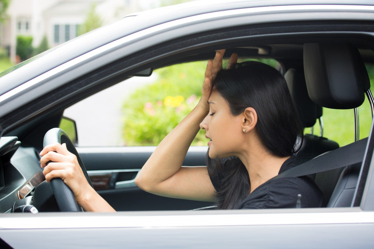 Closeup portrait, angry young sitting woman pissed off by drivers in front of her, hand on head, isolated city street background. Road rage traffic jam driving health