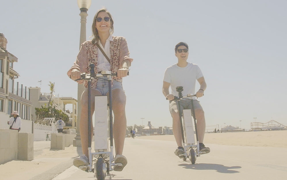 Couple rides URB-E foldable electric scooters along the beach in santa monica california