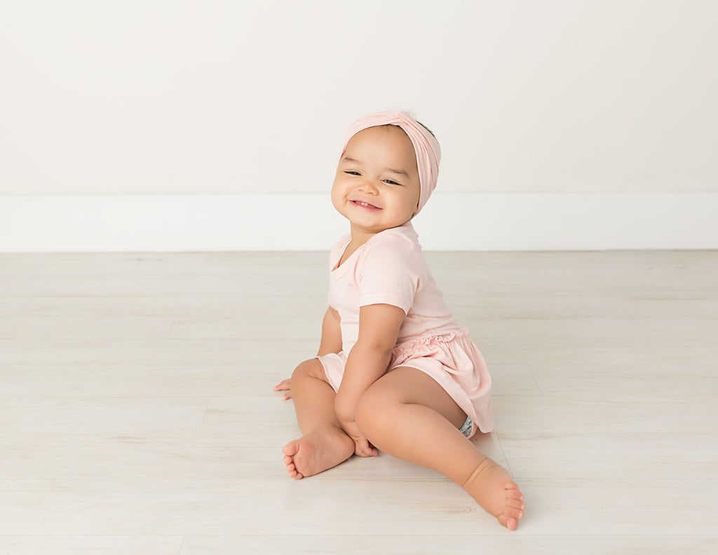 cute baby girl in blush pink bodysuit standing