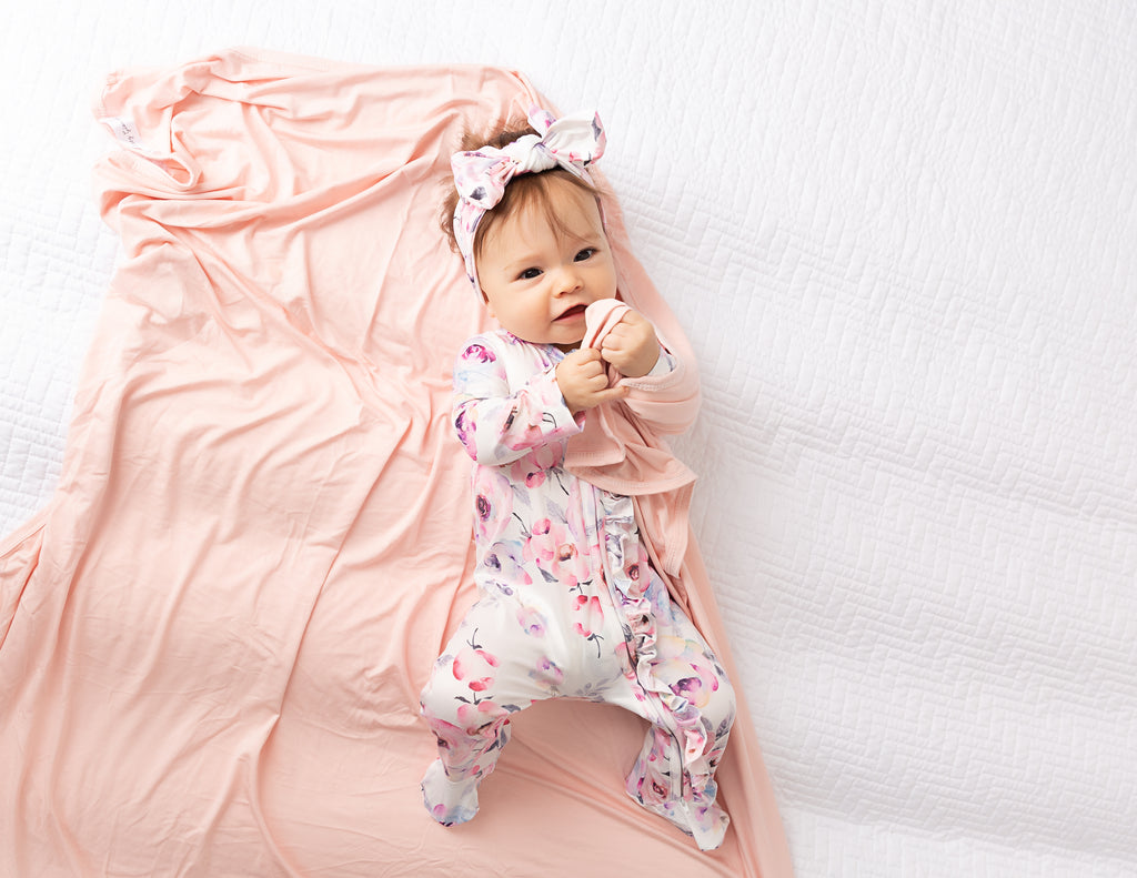 baby girl with blush pink swaddle blanket