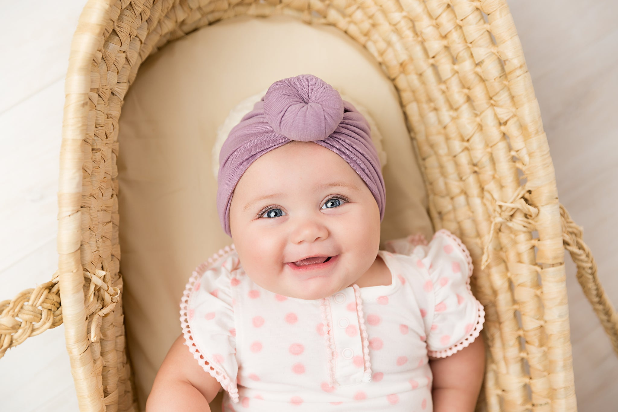 baby happy in crib and turban hat