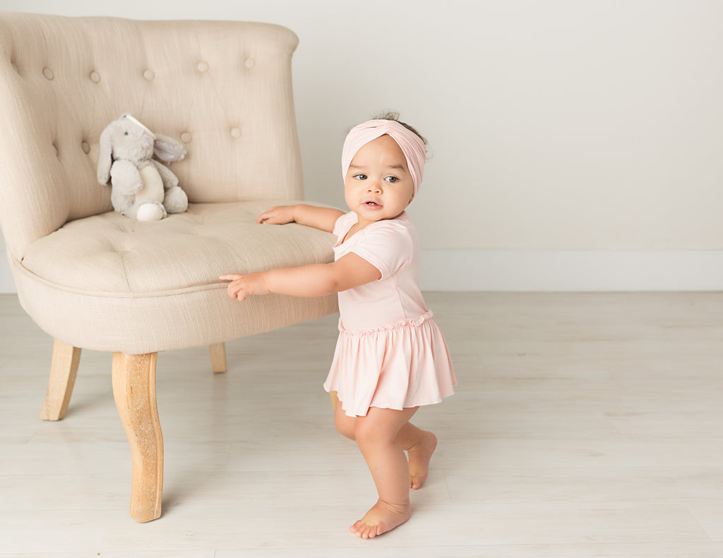 baby girl in blush pink bamboo fabric bodysuit with skirt