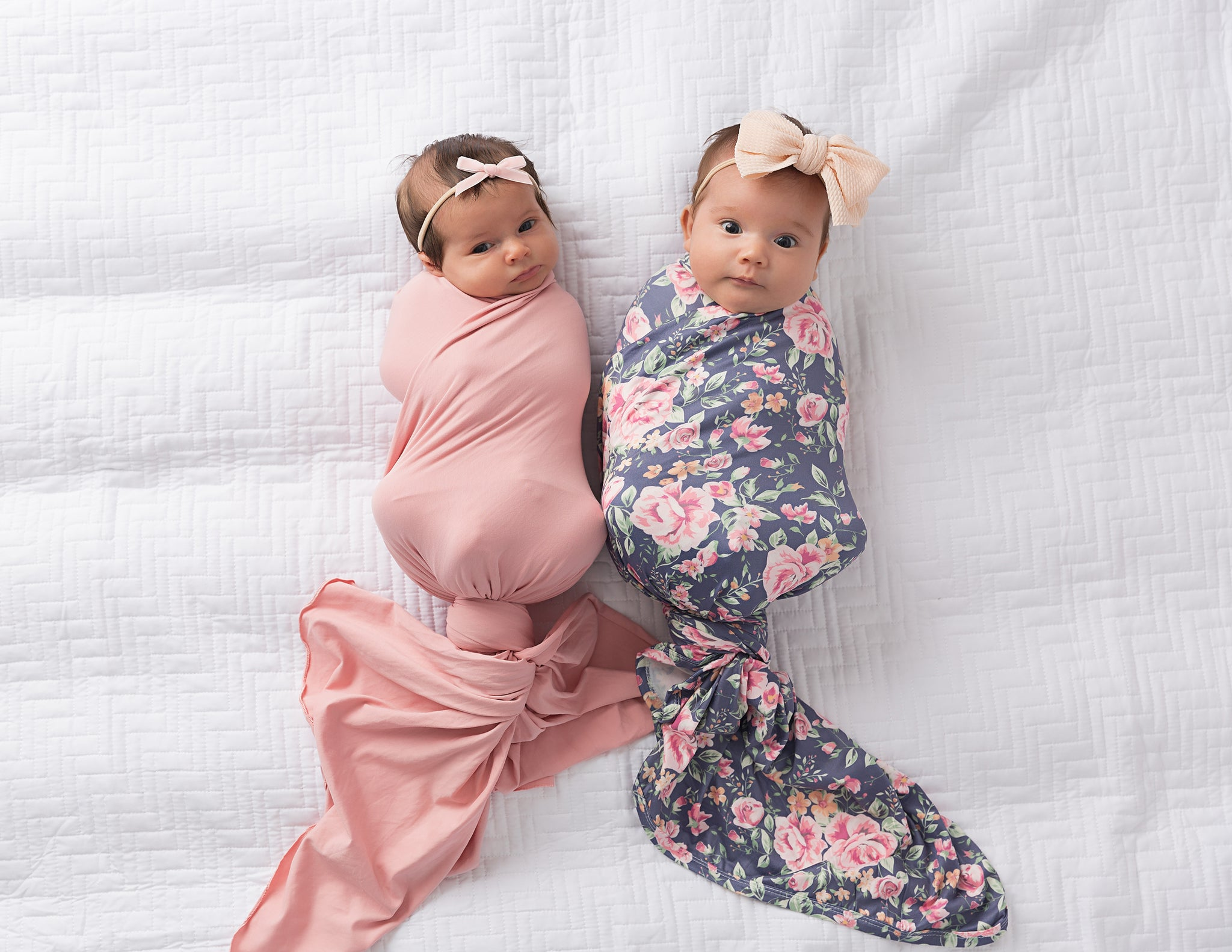 two babies in floral knot swaddle blankets