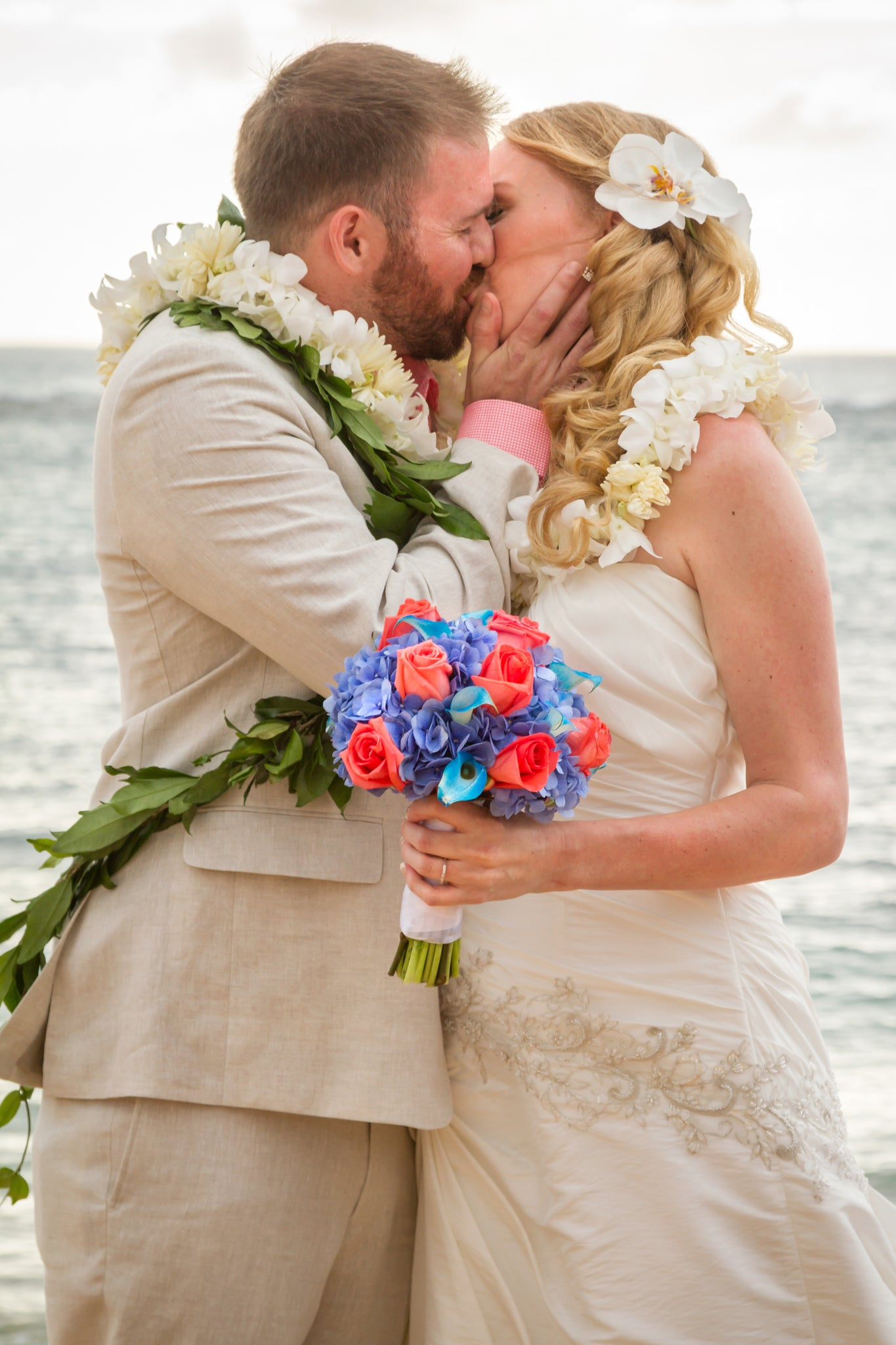 You may kiss the Bride. A Bride and Groom kiss on the beach in Hawaii